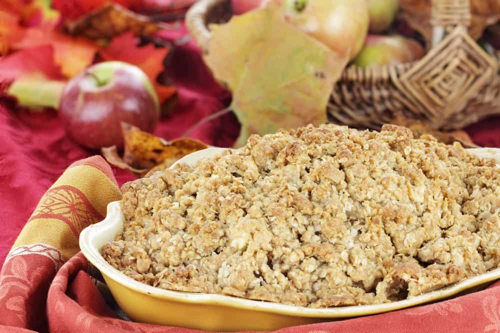 Freshly baked apple crisp with fresh apples and autumn leaves in the background.