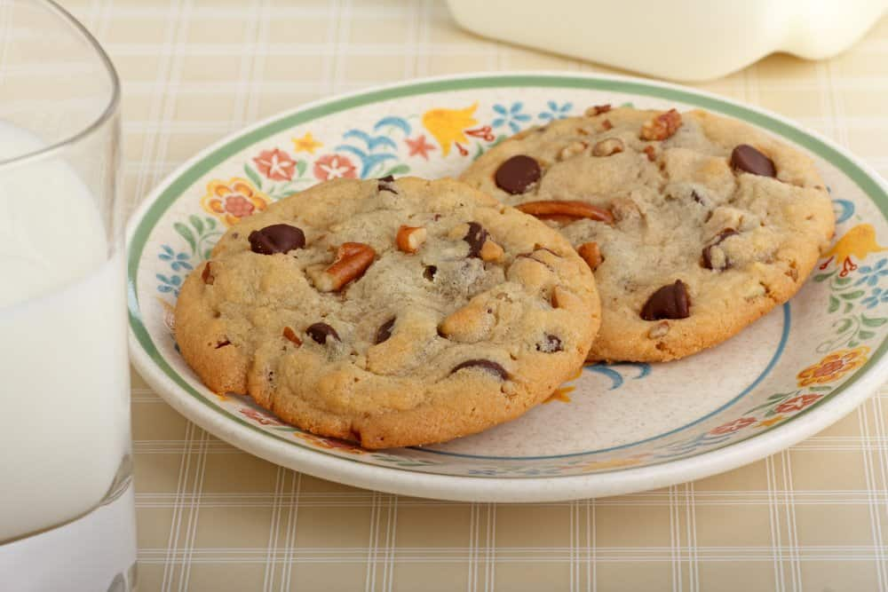 A plate with two chocolate chip pecan no-bake cookies on a table with a glass of milk.