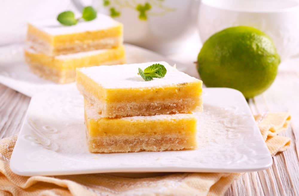 Two lime pie bars on a white plate.