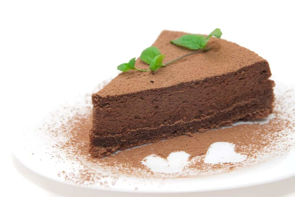A slice of no-bake chocolate cheesecake on a white plate.