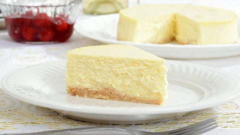 A slice of New York style cheesecake on a white plate with a fork and the rest of the cheesecake in the background.