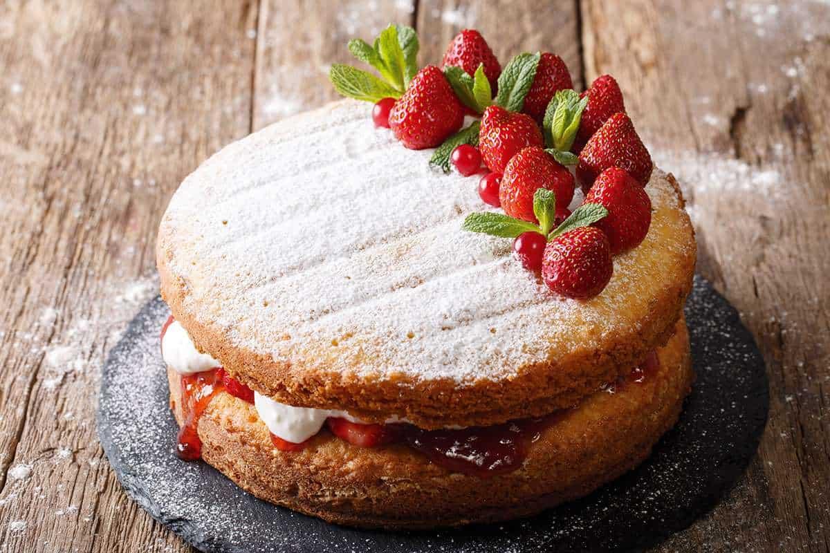 A strawberry sponge cake on a table.