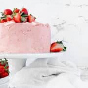A lemon and strawberry cake on a cake stand.