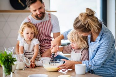 A mother, father and their two young children baking together at the kitchen table.