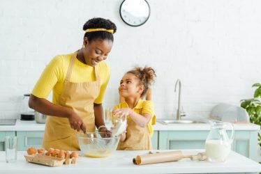 A mother and daughter baking together at the kitchen table.